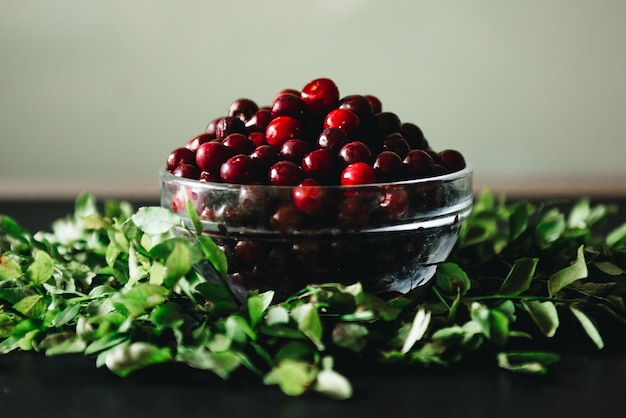Cherries in a glass bowl with twigs and leaves on a dark. healthy fresh, seasonal fruit to eat.