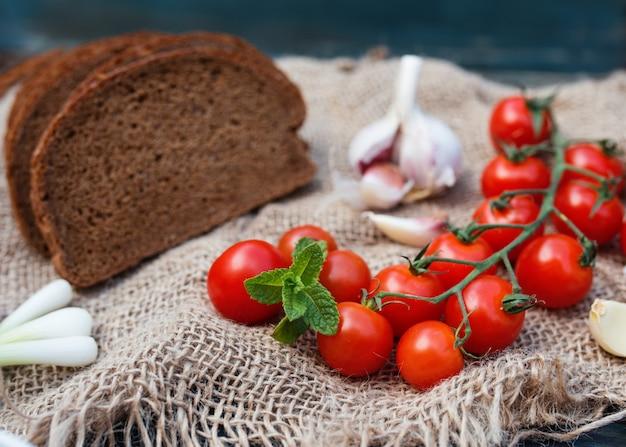 Вишня, серый хлеб, зеленый лук, чеснок на темном деревенском фоне