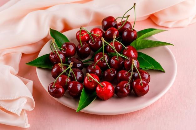 분홍색과 섬유 표면에 나뭇잎 높은 각도보기와 함께 접시에 체리