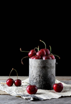 Cherries inside a vintage tin cup with old newspaper underneath