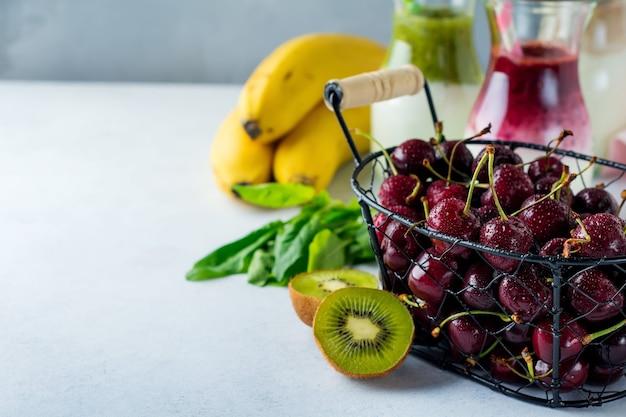 Вишня, киви, шпинат, банан, ингредиенты для фруктовых смузи на светлом фоне бетона место для текста.