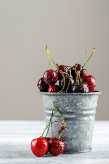 Cherries in a mini bucket on grunge and grey surface, side view.