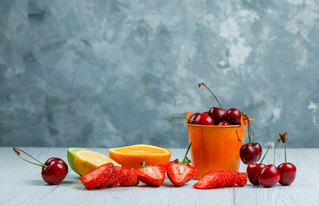 Cherries in a mini bucket with lemon, lime, orange, strawberries side view on wooden and grunge background