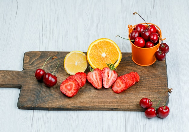 Cherries in a mini bucket with lemon, orange, strawberries flat lay on wooden and cutting board