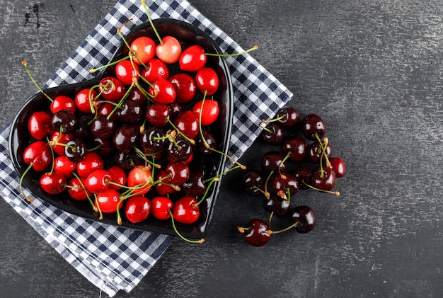 Cherries in a plate flat lay on picnic cloth and grey surface