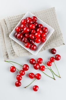 Cherries in a plate on white and kitchen towel