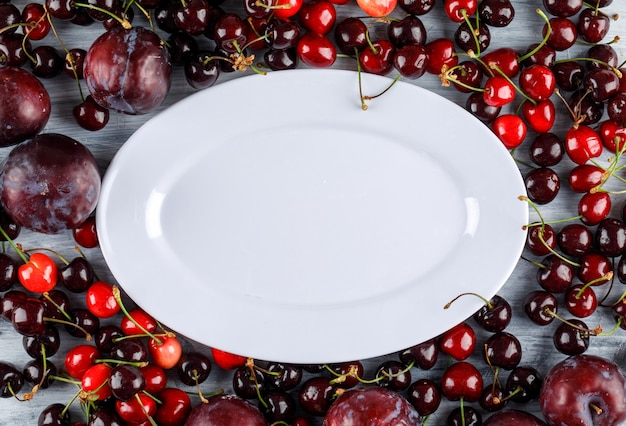 Cherries and plums with empty plate on grunge surface, flat lay.