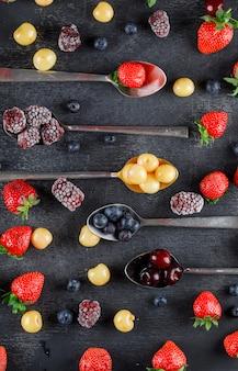 Cherries in spoons with strawberries, blueberries, mulberries flat lay on a dark table