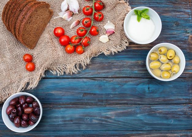 Вишня, зеленый лук, кориандр, сыр, чеснок, оливки в миске, хлеб на темном деревенском деревянном фоне.