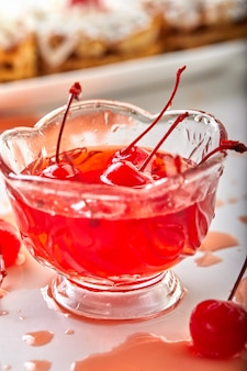 Cherries in sugar with sprigs in a cherry syrup in a transparent bowl