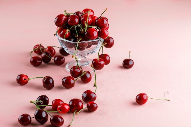 Cherries in a vase on a pink surface