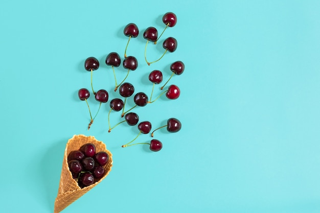 Cherries in waffle cone on blue background top view