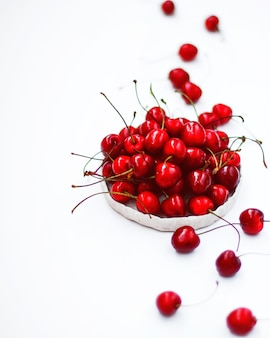 Cherries in white handmade ceramic rustic bowl.
