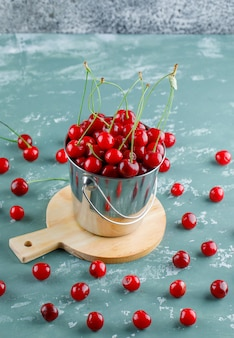 Cherries with cutting board in a bucket on plaster and grungy space, high angle view.