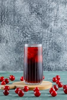 Вишни с разделочной доской, сок на штукатурке и шероховатый пространство, вид сбоку.