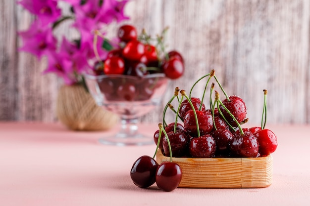 Cherries with flower pot in wooden plate and vase on pink and grunge surface, side view