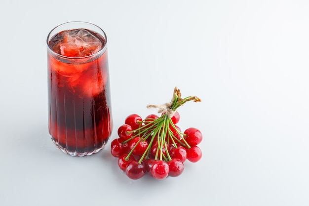 Cherries with icy drink high angle view on a white space