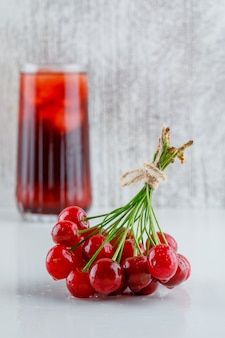 Cherries with icy drink side view on white and grungy space