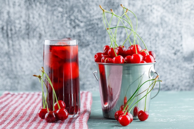 Cherries with juice, kitchen towel in a bucket on plaster and grungy space, side view.