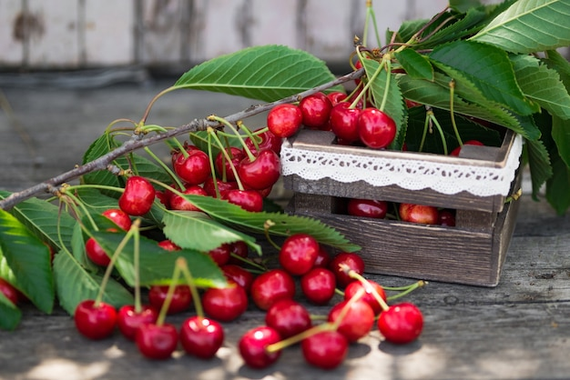 Вишни с листьями в старинном деревянном ящике на деревенском деревянном столе. скопируйте пространство.