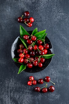 Cherries with leaves in a plate on grey surface, top view