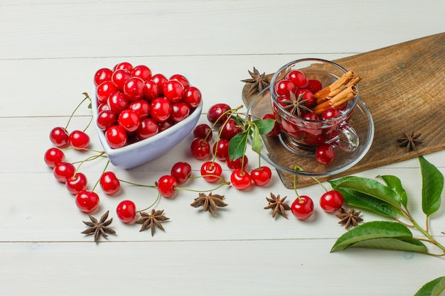 Cherries with leaves, spices in bowl and glass on wooden and cutting board, high angle view.