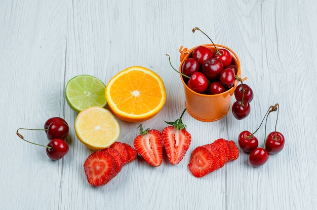 Cherries with lemon, lime, orange, strawberries in a mini bucket on wooden table, flat lay.