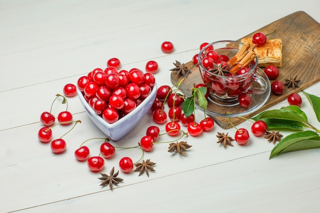 Cherries with pastry, leaves, spices in bowl and glass on wooden and cutting board, high angle view.