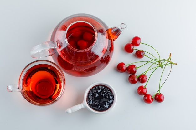Cherries with tea, jam on white space, flat lay.