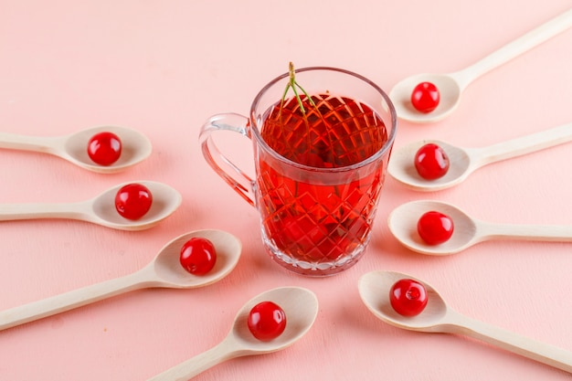 Cherries with tea in wooden spoons on pink space, high angle view.