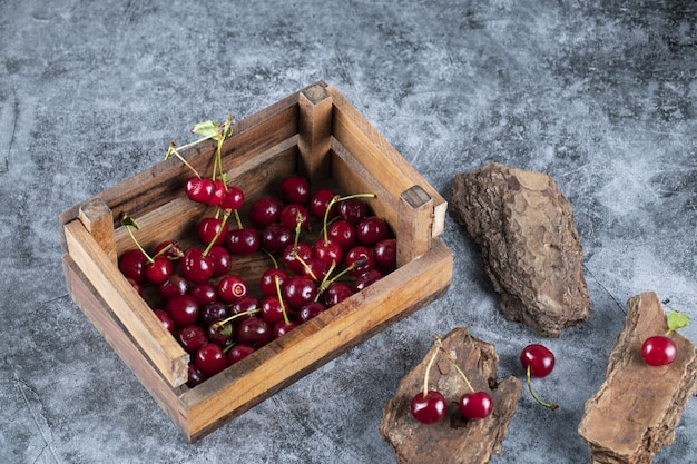 Cherries in a wooden basket on the marble