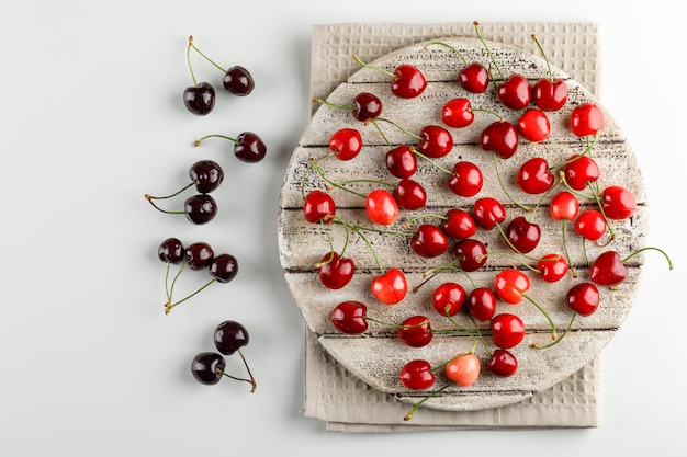 Cherries on a wooden board on white and kitchen towel surface. flat lay.