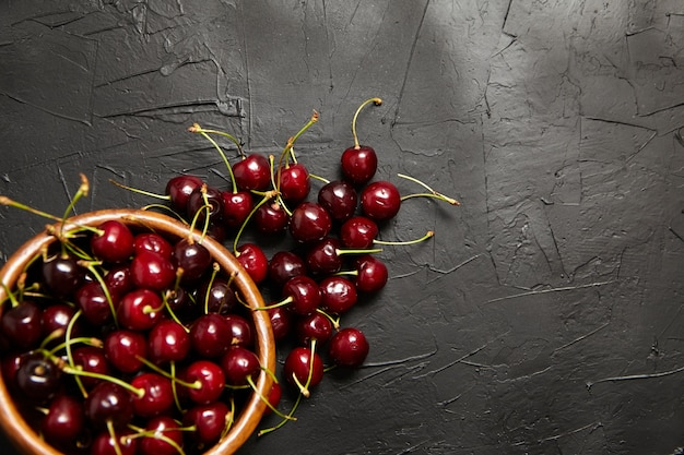Cherries in a wooden bowl on a black stone table