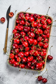 Cherries in a wooden bowl. fresh ripe cherries. gray background. top view.