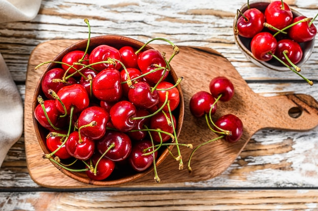 Cherries in a wooden bowl. fresh ripe cherries. white background. top view.