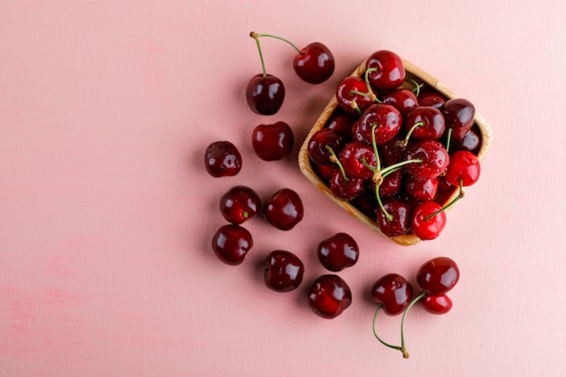 Cherries in a wooden plate on pink surface