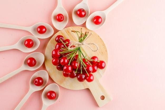 Le ciliegie in cucchiai di legno piatti giacciono sul rosa e sul tagliere