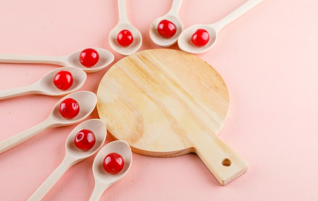 Cherries in wooden spoons on pink and cutting board space. high angle view.