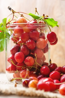 Cherries on wooden table in glass jar