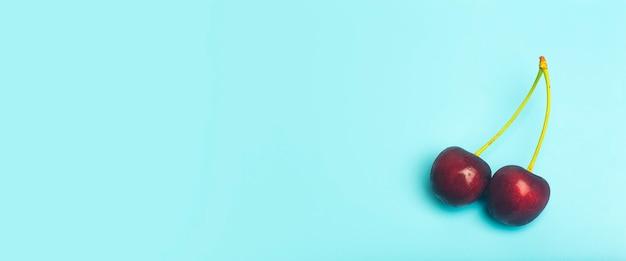 Вишневый фон. красная сочная черешня на голубом фоне. летние свежие сочные ягоды и концепция питания. фото высокого качества