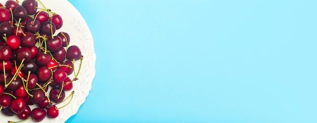 Вишневый баннер фон. красная сочная черешня на белой тарелке на голубом фоне. летние свежие сочные ягоды и концепция питания. фото высокого качества