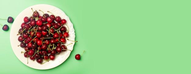 Вишневый баннер фон. красная сочная черешня на белой тарелке на светло-зеленом фоне. летние свежие сочные ягоды и концепция питания. фото высокого качества