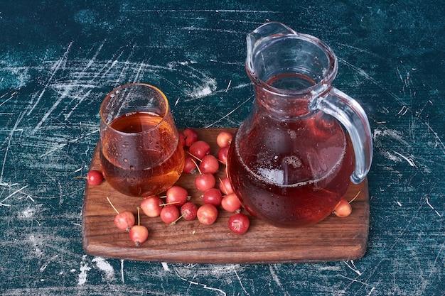 Ягоды вишни с чашкой напитка на синем.