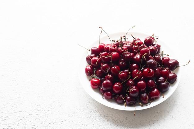 Черри берри на белом фоне. ягоды на тарелку на белом фоне.