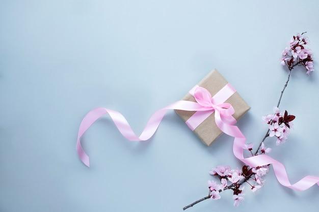 Вишневый цвет и подарочная коробка с розовой лентой на светло-серой стене