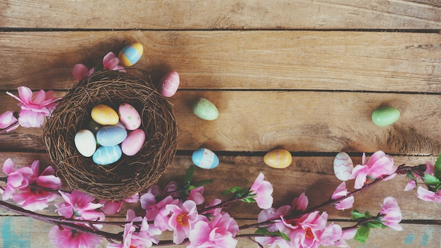 Cherry blossom artificial flowers and easter egg in nest on vintage wooden background with copy space.