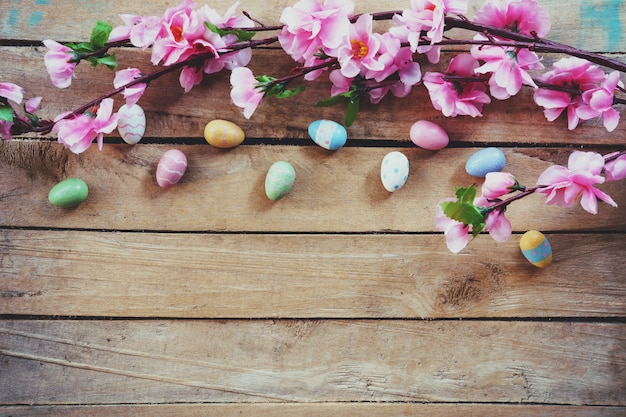 Cherry blossom artificial flowers and easter egg on vintage wooden background with copy space.