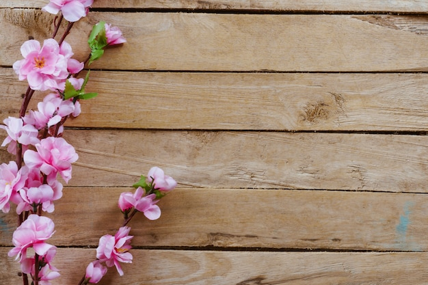 Cherry blossom and artificial flowers on vintage wooden background with copy space.