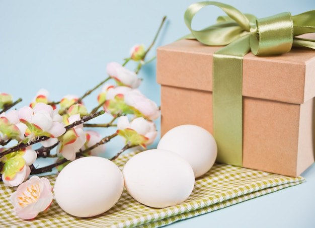 Cherry blossom branch sakura, eggs and gift box for easter day. copy space.