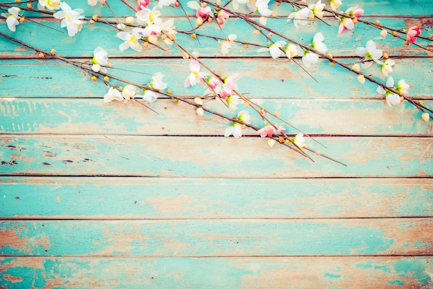 Cherry blossom flowers on vintage wooden background, border design.